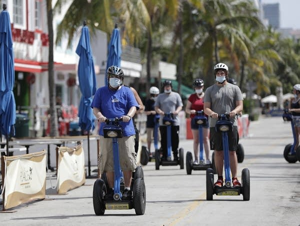 A tour group on Segways rides down Florida's famed Ocean Drive