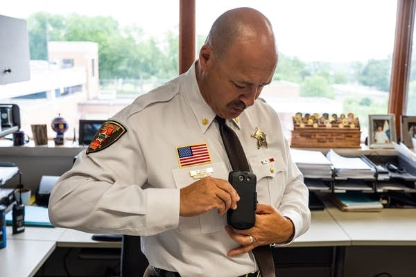 A police officer in a white shirt clips a body camera onto his tie.
