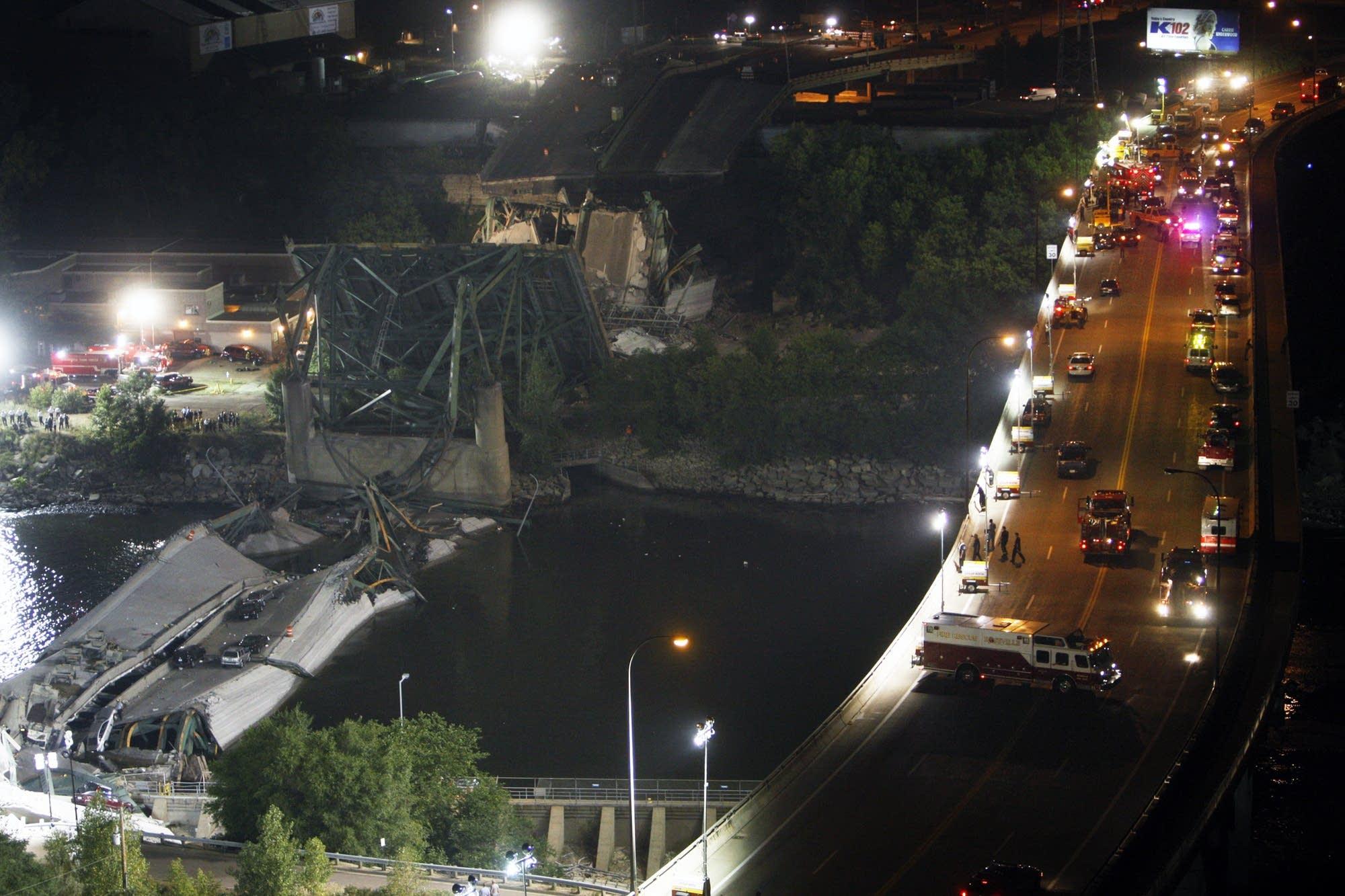 Spotlights illuminate the collapsed Interstate 35W bridge.