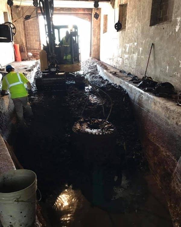 Crews excavate debris and pump out water