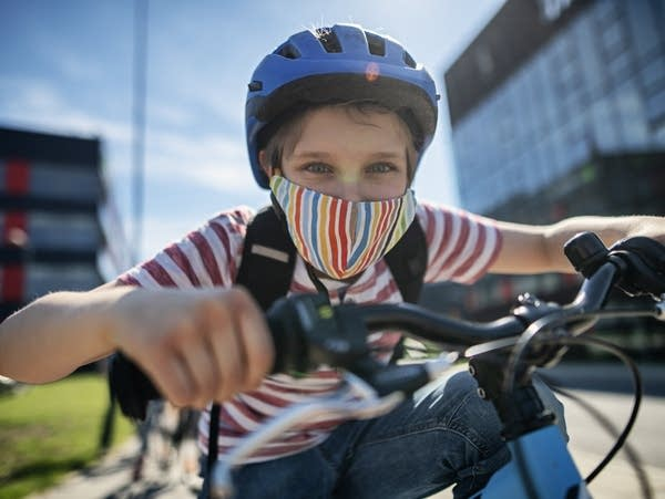 A kid riding a bike in a helmet and face mask