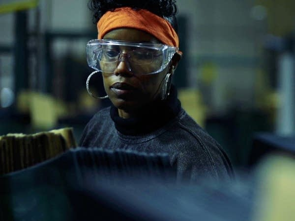 A woman wears safety glasses surrounded by manufacturing equipment.