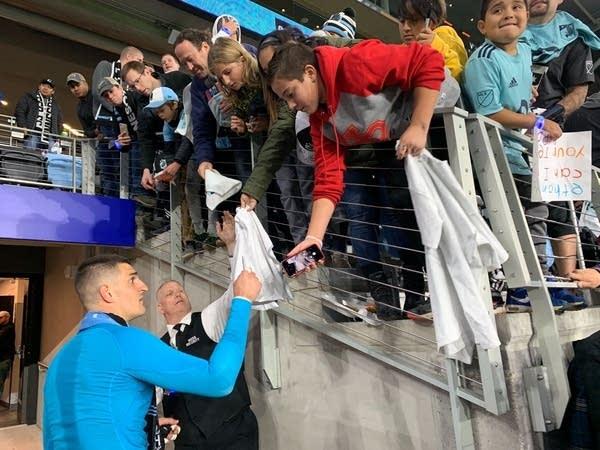 Fan reach over a barricade as a soccer player signs autographs.