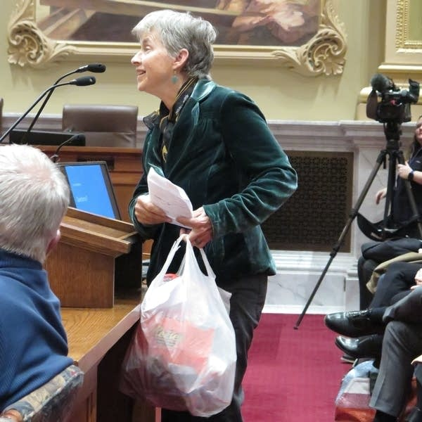 A woman holding a plastic bag testifies before a City Council committee.