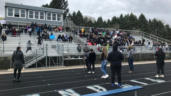 A collection of students gather to sit on bleachers.
