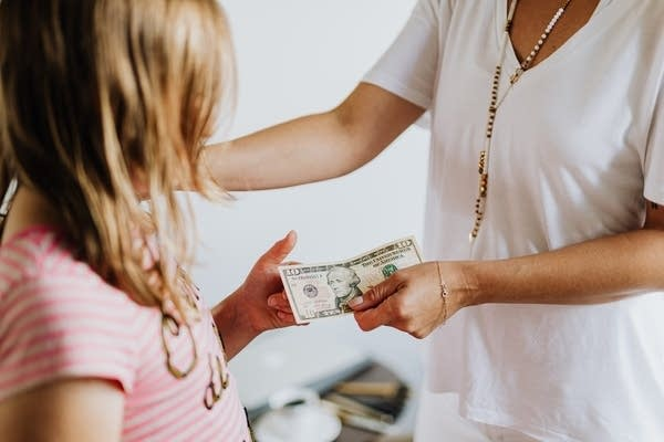 An adult hands cash to a girl.