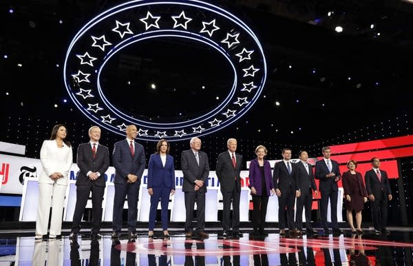 Candidates stand on a stage.