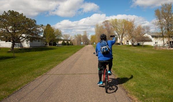 a man biking along a path holding a phone to take a selfie