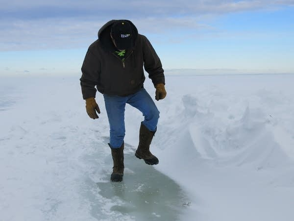 A man checks on ice on Lake Winnibigoshish.