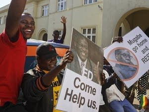 Protesters calling for the impeachment of Robert Mugabe ride on a minibus.
