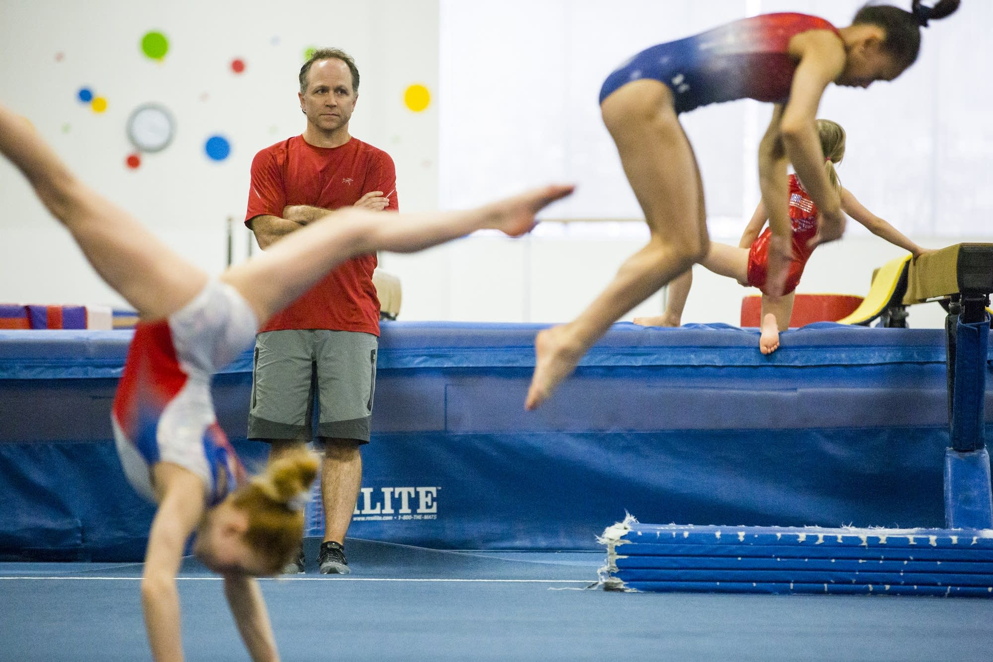 Coach Jess Graba watches gymnasts practice.