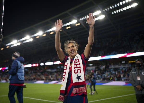 A soccer player waves on the field.