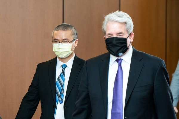 Two men in suits and masks.