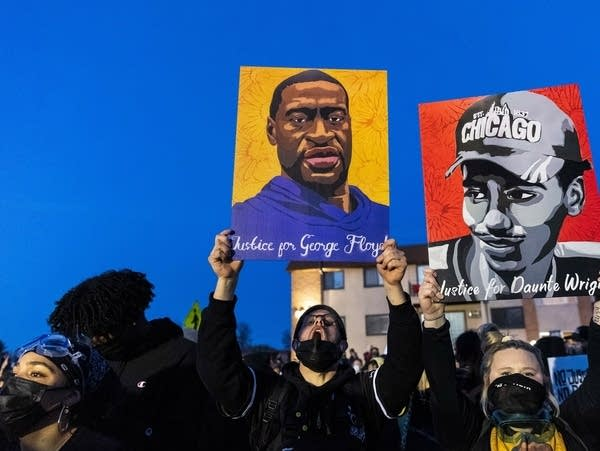 Demonstrators hold portraits of George Floyd and Daunte Wright