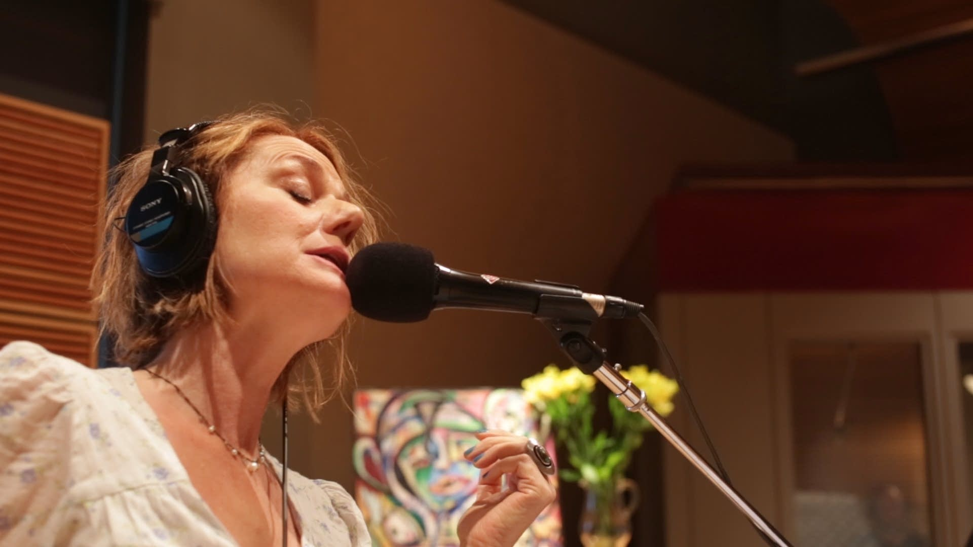 Gretchen Seichrist sings in front of one of her paintings.