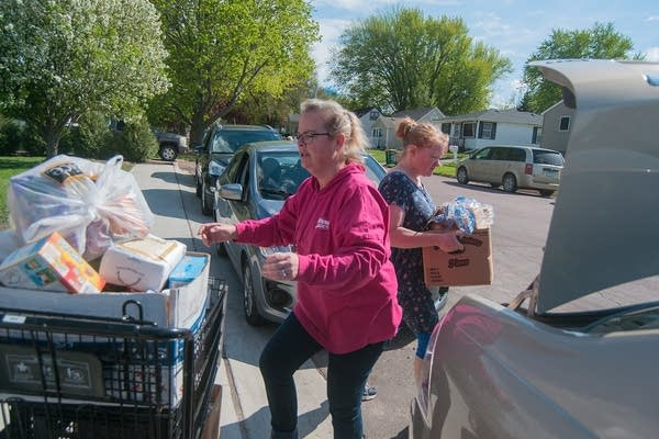Two people load boxes of food in a car.