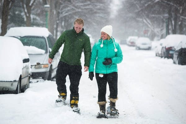 Two people walk with their snowshoes