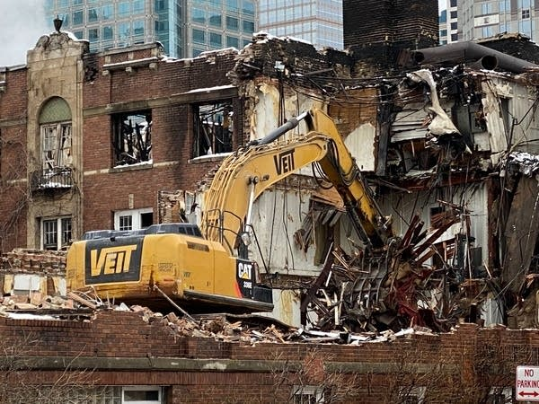 A crane knocks down a damaged building.