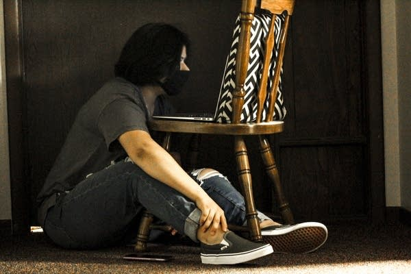 A person sits on the floor and looks at a laptop in a chair.