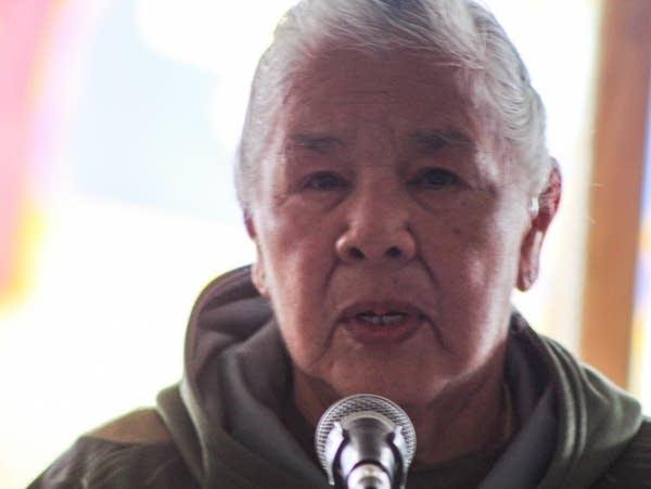 A veteran stands at a microphone to speak.