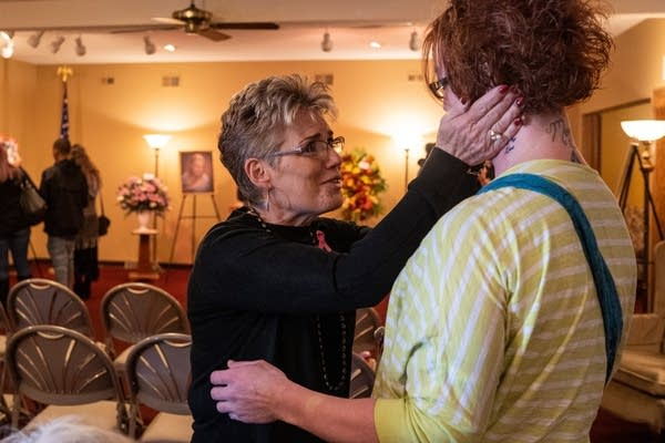 A woman reaches up to the face of another with both hands.
