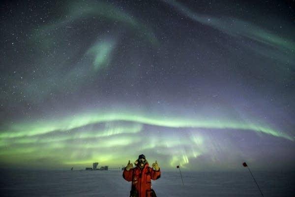 Robert Schwarz gives the thumbs up under bright auroras.