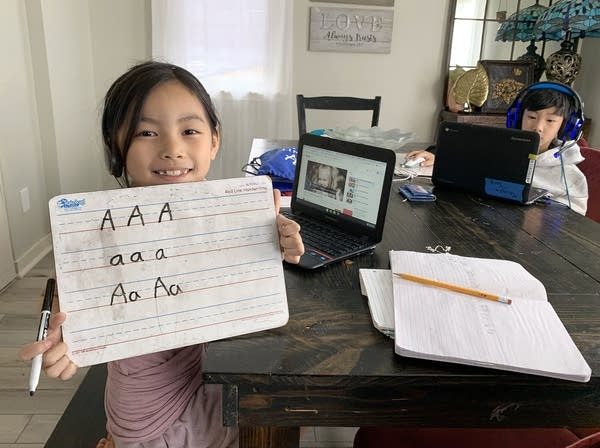 "A young girl holds up a white board with handwritten letter ""A""s."