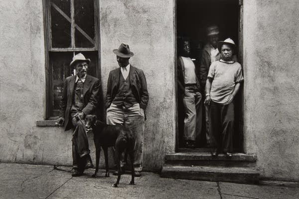 A black and white photograph of men outside of a pool hall.