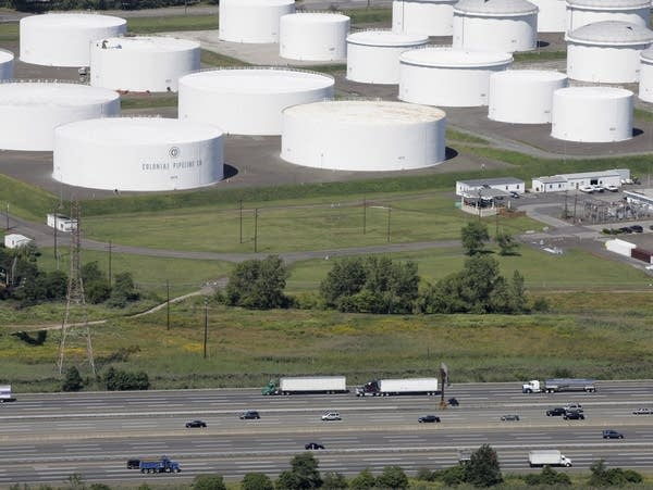 Traffic passes oil storage tanks