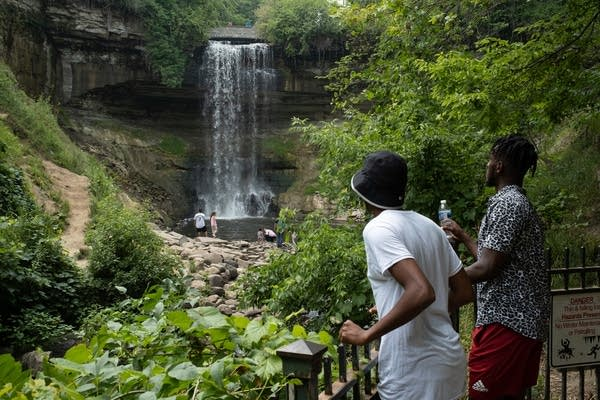 People look at a waterfall.