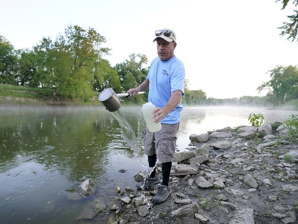 A man takes a water sample from a river
