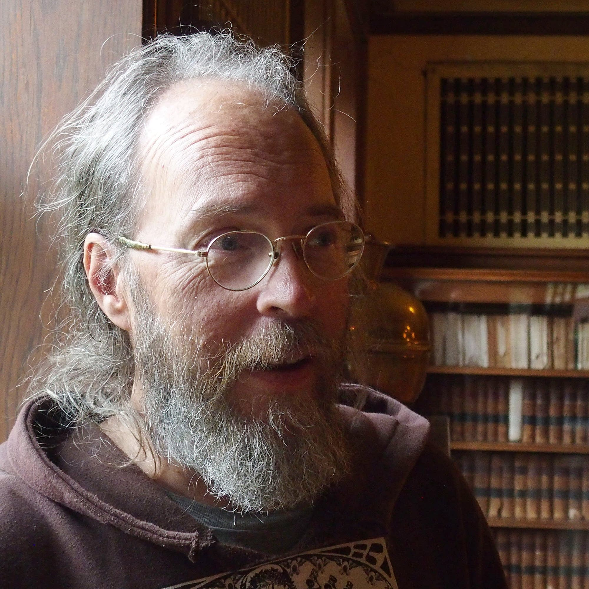 Charlie Parr stands in front of a bookshelf.