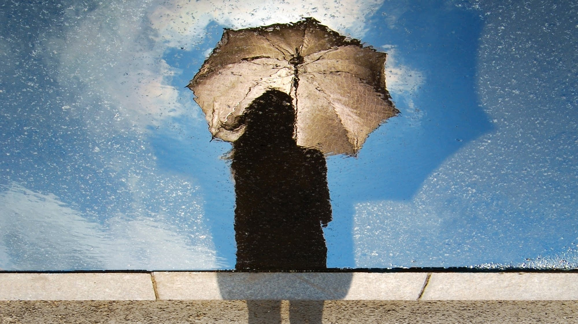 A reflection of a woman with an umbrella