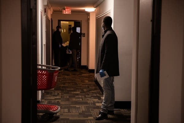 Abdullahi Khalif stands at a distance in a hallway.