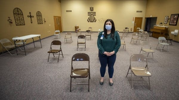 A woman wearing a mask stands in a room amid spaced-out folding chairs