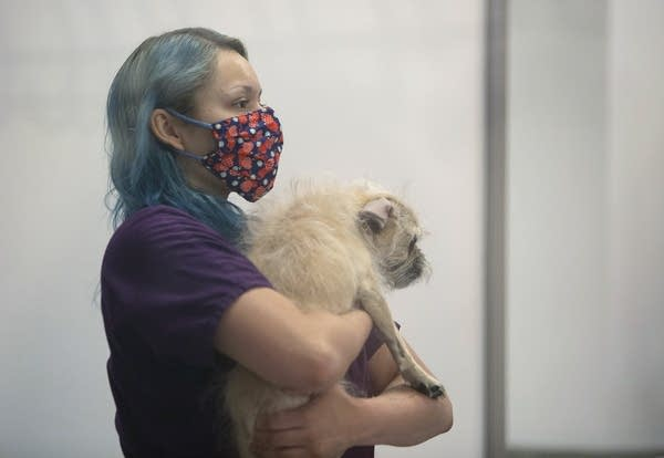 A woman wearing a face mask holds a dog.