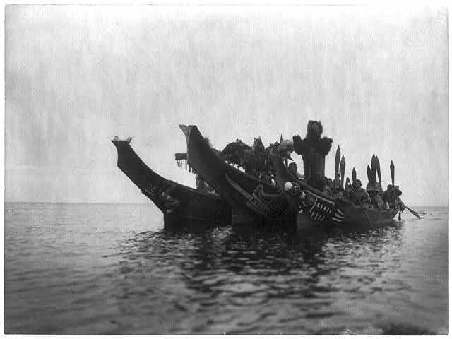 Masked dancers in canoes