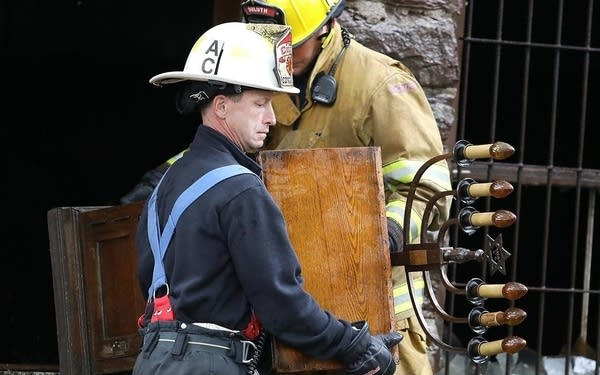 Duluth Assistant Fire Chief Dennis Edwards helps firefighter Ben Johnson.