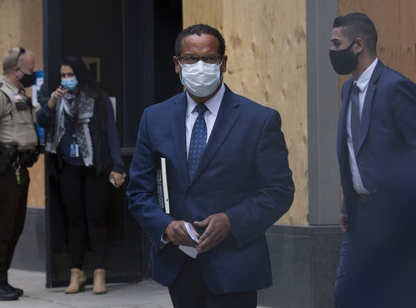 A man wearing a suit and face mask walks out of a building