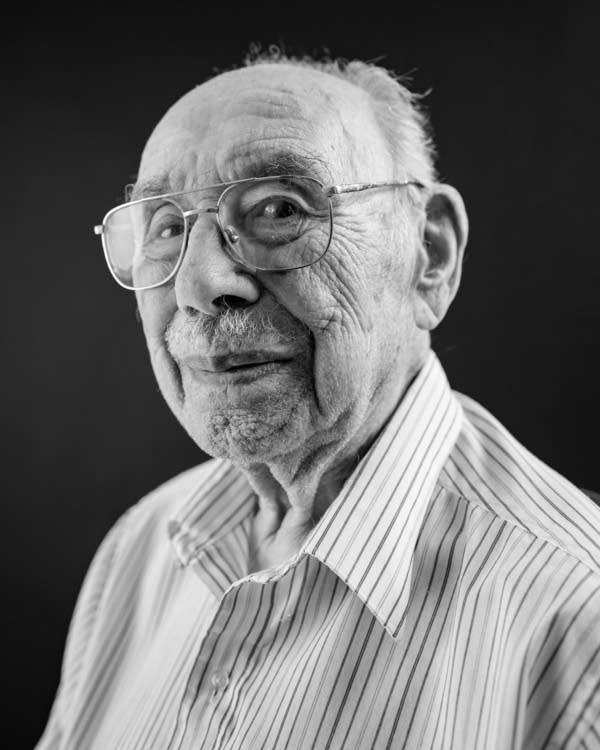 A black and white headshot of a man in glasses.