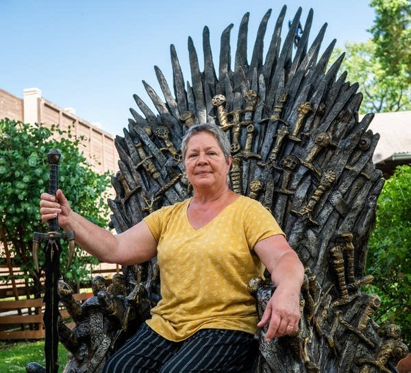 Gail Janes of sits in a replica of the Iron Throne.