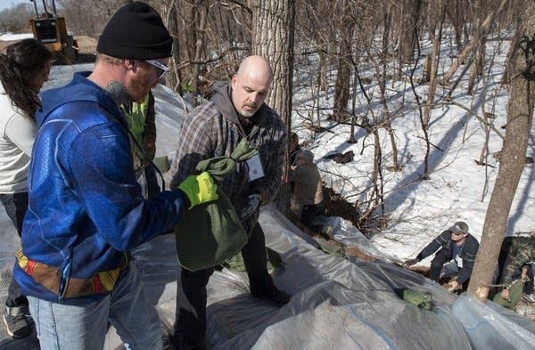 James Hause and Matt Olson use sandbags to hold down plastic on a berm.