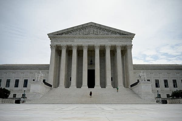 A woman walks down steps at the Supreme Court.