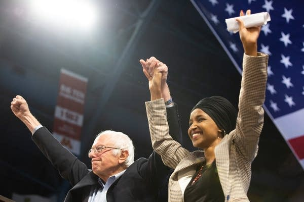 A man and a woman lift their hands in the air.