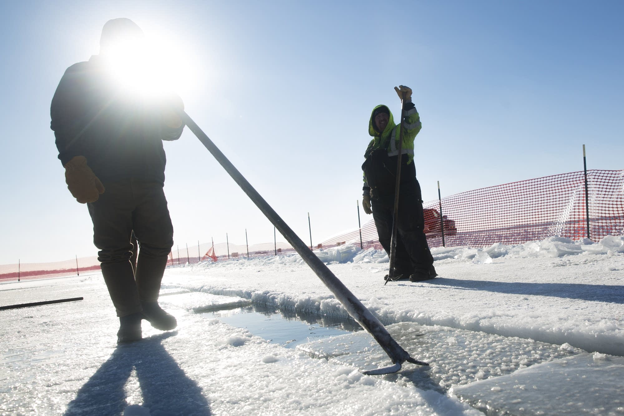 A volunteer uses an ice pick to push blocks of ice.