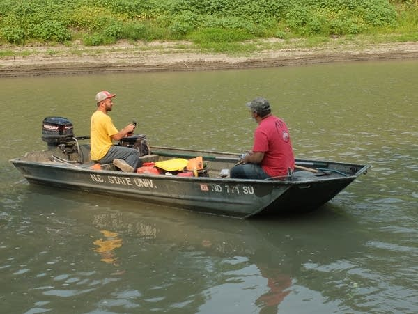 two men in a boat on a river
