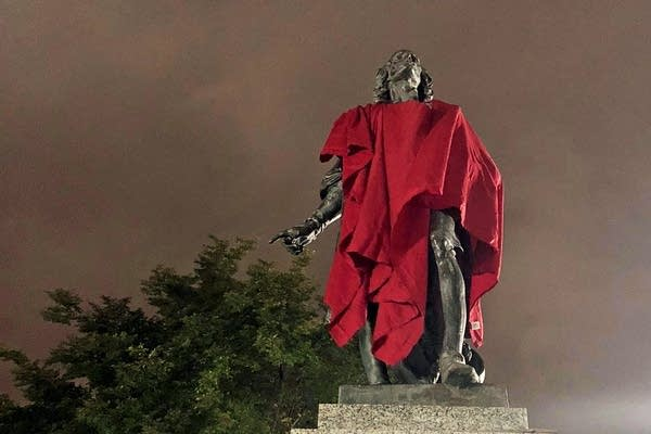 A statue of Christopher Columbus adorned with a red sheet.