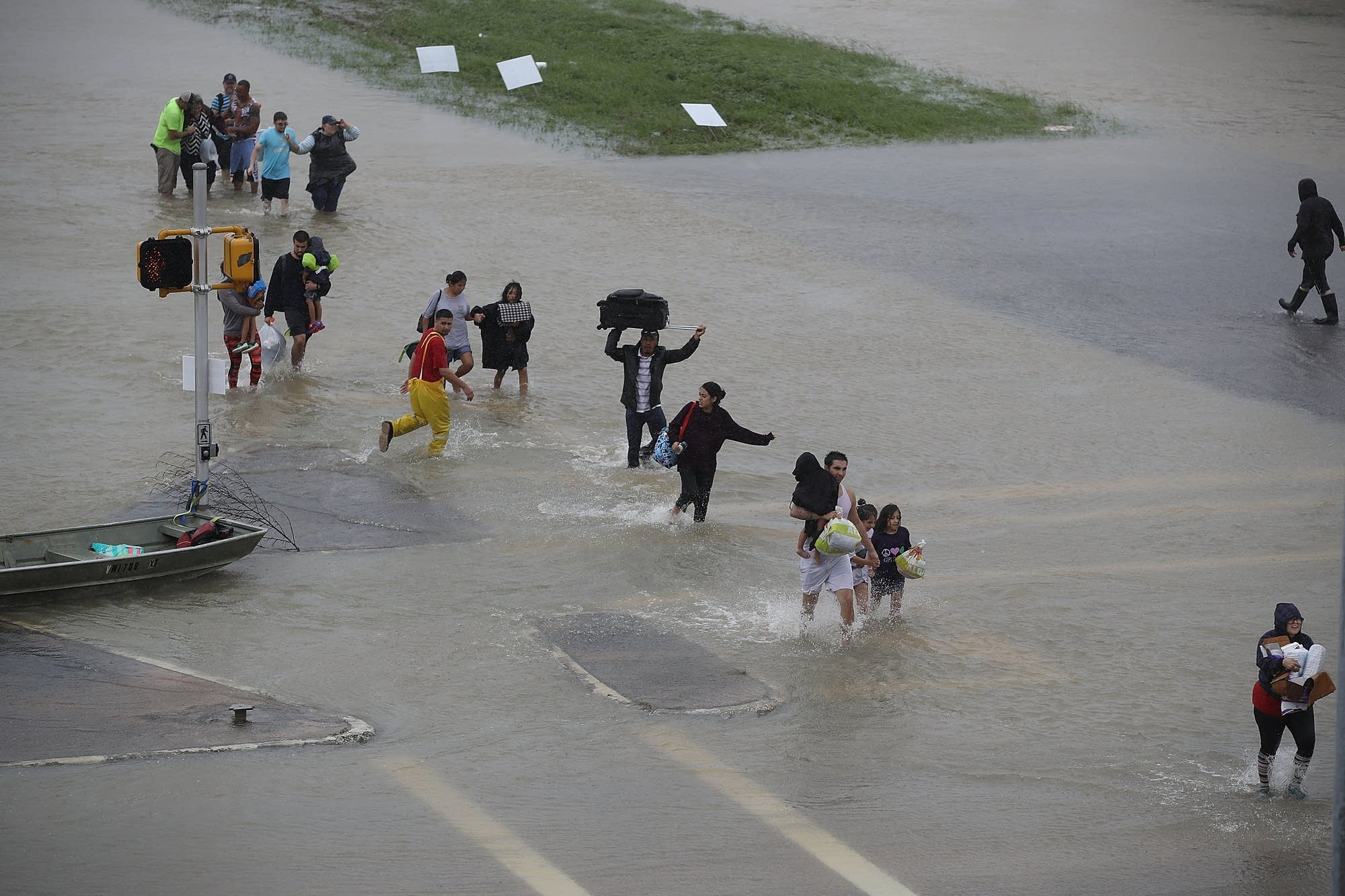 People walk down a flooded street as they evacuate their homes.