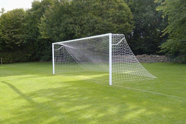 A soccer goal w/ net on empty soccer field