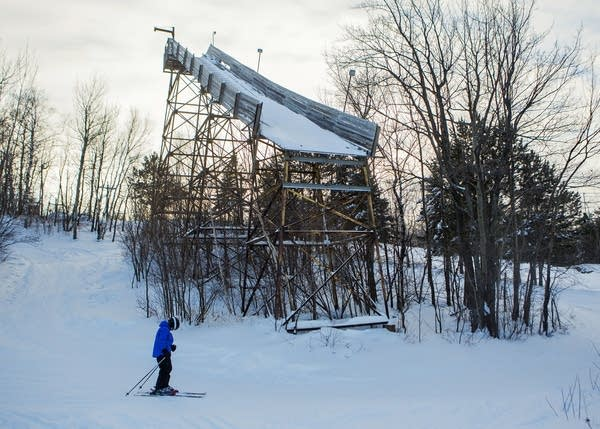A skier glides past an old ski jump